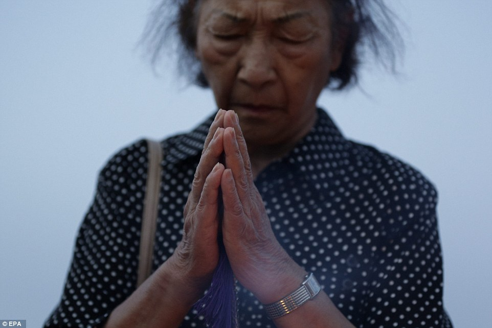 2B23695000000578-3186815-A_woman_is_seen_deep_in_prayer_at_Hiroshima_s_Peace_Memorial_Par-a-91_1438857513515