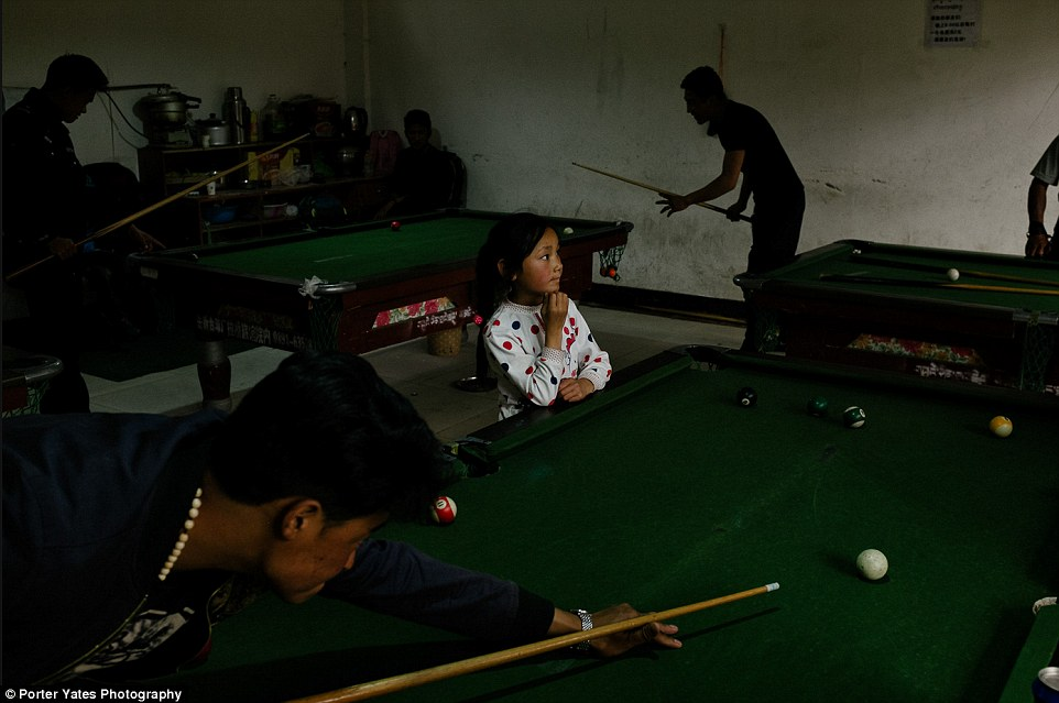 2D04B91000000578-3257757-A_young_girl_watches_men_play_pool_inside_a_billiards_hall_in_Ga-a-96_1443800113810