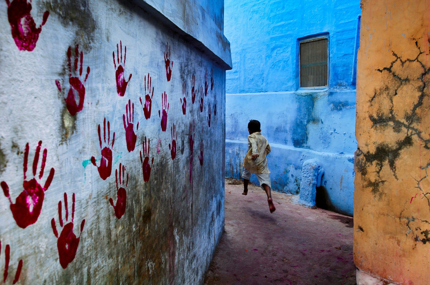Boy in mid-flight, Jodhpur, India, 2007 At the foot of the vast Mehrangarh Fort, one can find the Blue City, a small tightly knit maze of houses located towards the north of Jodhpur. In one of the narrow alleyways a boy flees McCurry's camera. Balancing three intersecting planes of colour - one of which is covered in stark red handprints - the image pulsates with energy as a young boy dashes through the narrow alleyways. At the foot of the vast Mehrangarh Fort, one can find the Blue City, a small tightly knit maze of houses located towards the north of Jodhpur. Balancing three intersecting planes of colour - one of which is covered in stark red handprints - the image pulsates with energy as a young boy dashes through the narrow alleyways. Phaidon, The Unguarded Moment, Iconic Photographs, IP page 6, final print_poster