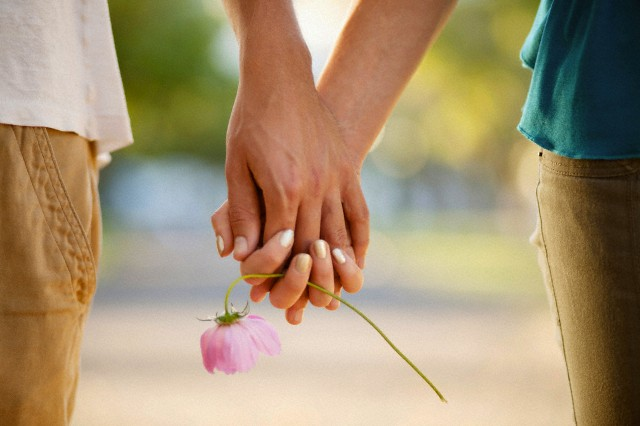 10 Jan 2012 --- Couple holding hands and flower --- Image by © Yuri Arcurs/Tetra Images/Corbis