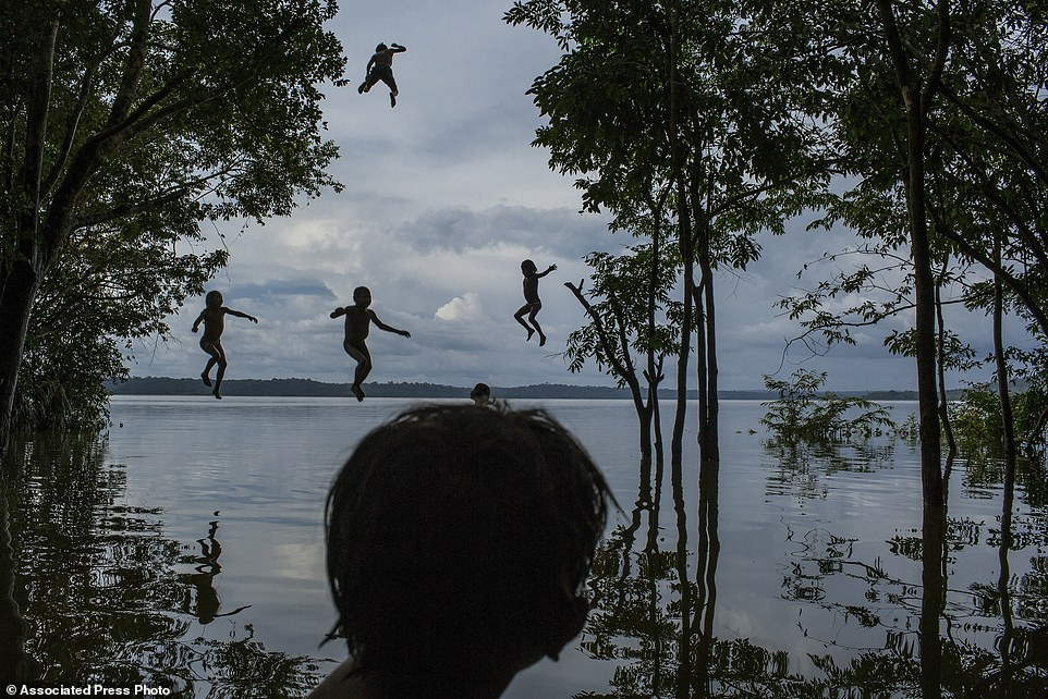 "In this image released by World Press Photo titled ""Amazon's Munduruku Tribe"" by photographer Mauricio Lima for The New York Times which won second prize in the Daily Life singles category shows indigenous Munduruku children playing in the Tapajos river in the tribal area of Sawre Muybu, Itaituba, Brazil, Feb. 10, 2015. The tribesmen of the Munduruku, who for centuries have sanctified the Tapajos River on which their villages sit, are fighting for survival. Brazil's government plans to flood much of their land to build a $9.9 billion hydroelectric dam, the Sao Luiz do Tapajos, as part of a wider energy strategy across the Amazon rainforest. (Mauricio Lima/The New York Times, World Press Photo via AP)"