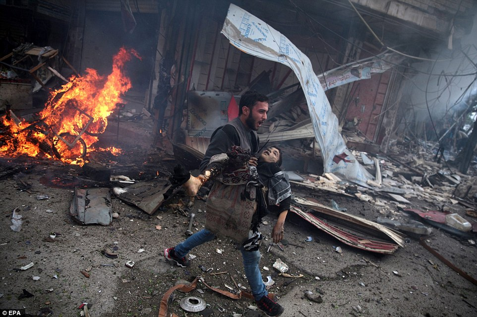 31571EBE00000578-3452659-The_picture_shows_a_Syrian_man_carrying_the_body_of_a_child_kill-a-32_1455813040173