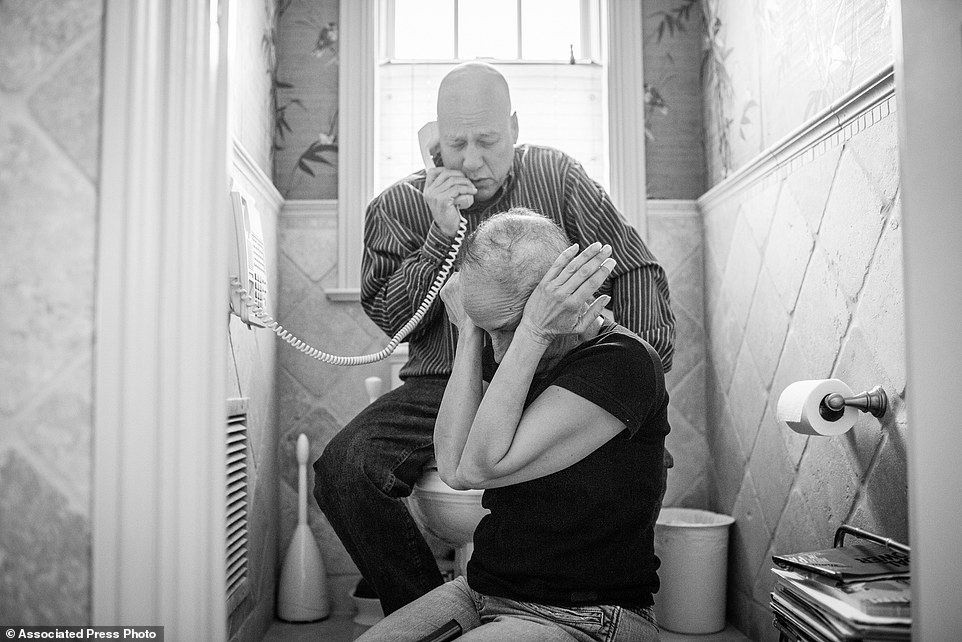 "In this image released by World Press Photo titled ""A Life in Death"" by photographer Nacy Borowick which won second prize Long Term Projects shows Howie and Laurel Borowick sitting next to the bathroom telephone as they receive the most recent news from their oncologist. New York, US, March 8, 2013. A daughter photographs her own parents who were in parallel treatment for stage-four cancer, side by side. The project looks at love, life, and living, in the face of death. It honors their memory by focusing on their strength and love, both individually and together, and shares the story of their final chapters, within a year of each other. (Nancy Borowick, World Press Photo via AP)"