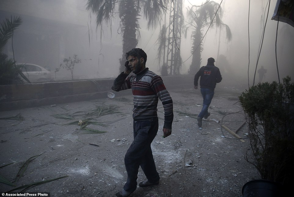 "In this image released by World Press Photo titled ""Aftermath of Airstrikes in Syria"" by photographer Sameer Al-Doumy for AFP which won the first prize in the Spot News stories category shows a wounded man walking out of a dust cloud following reported airstrikes in the town of Hamouria, Syria, Dec. 9, 2015.(Sameer Al-Doumy/AFP, World Press Photo via AP)"