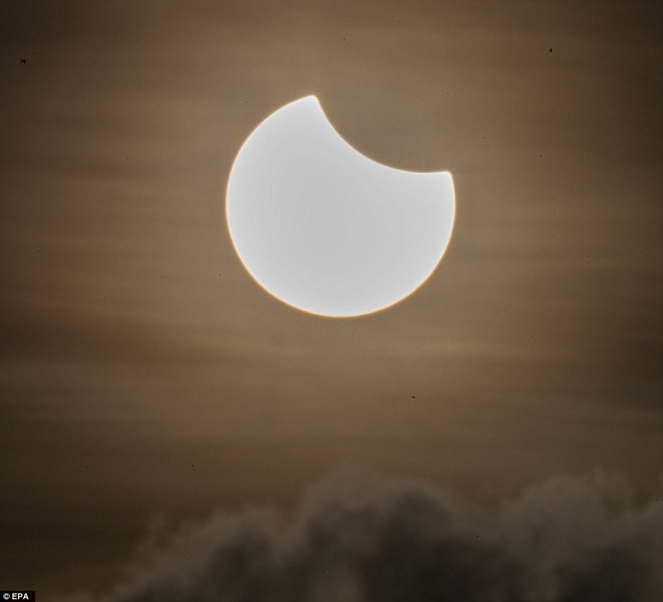 3203573700000578-3482995-A_partial_solar_eclipse_is_pictured_above_a_cloud_formation_at_d-a-1_1457509410387